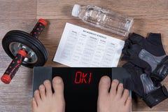 Αρσενικά πόδια στις ψηφιακές κλίμακες με τη λέξη που περιβάλλονται εντάξει από τα αθλητικά εξαρτήματα και το μπουκάλι νερό Στοκ φωτογραφία με δικαίωμα ελεύθερης χρήσης