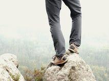 Αρσενικά πόδια στο σκοτεινό παντελόνι πεζοπορίας και παπούτσια οδοιπορίας δέρματος στην αιχμή του βράχου επάνω από τη misty κοιλά Στοκ Εικόνες