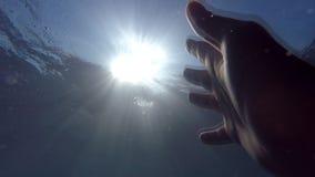 Αρσενικά τεντώματα χεριών από κάτω από το νερό στα sunrays Βραχίονας που ζητά τη βοήθεια και που προσπαθεί να φθάσει στον ήλιο Άπ φιλμ μικρού μήκους