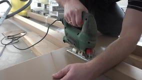 Αρσενικά χέρια εργαζομένων που κόβουν το φυλλόμορφο πίνακα δαπέδων με το ηλεκτρικό fretsaw απόθεμα βίντεο