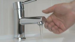 Αρσενικά χέρια που ανοίγουν καλυμμένη τη χρώμιο βρύση φιλμ μικρού μήκους