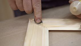 Αρσενικά χέρια που βάζουν τα κτυπήματα του χρώματος στην ελαφριά ξύλινη ένωση γωνιών πλαισίων απόθεμα βίντεο