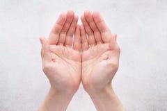 Αρσενικά χέρια που γίνονται κοίλα μαζί στο ανοικτό γκρι υπόβαθρο στοκ φωτογραφία με δικαίωμα ελεύθερης χρήσης
