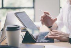 Αρσενικά χέρια που δακτυλογραφούν τον ηλεκτρονικό σταθμό πληκτρολόγιο-αποβαθρών ταμπλετών Blogger που λειτουργεί στον ξύλινο πίνα Στοκ φωτογραφία με δικαίωμα ελεύθερης χρήσης