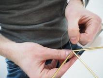 Αρσενικά χέρια που κάνουν μια δομή μετάλλων Στοκ Φωτογραφία