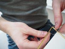 Αρσενικά χέρια που κάνουν μια δομή μετάλλων Στοκ Φωτογραφίες