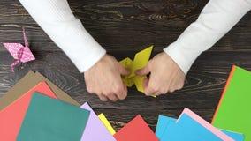 Αρσενικά χέρια που κάνουν την πεταλούδα origami φιλμ μικρού μήκους