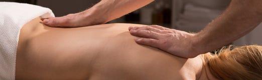 Αρσενικά χέρια που κάνουν το πίσω μασάζ Στοκ Φωτογραφία