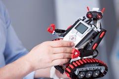 Αρσενικά χέρια που καθορίζουν λίγο χαριτωμένο droid Στοκ φωτογραφίες με δικαίωμα ελεύθερης χρήσης