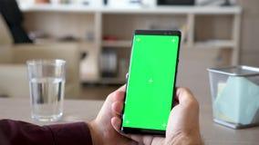 Αρσενικά χέρια που κρατούν ένα smartphone με την πράσινη χλεύη χρώματος οθόνης επάνω φιλμ μικρού μήκους