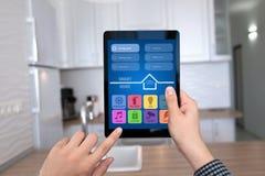 Αρσενικά χέρια που κρατούν την ταμπλέτα με app το έξυπνο σπίτι εγχώριων κουζινών Στοκ Εικόνα