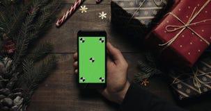 Αρσενικά χέρια που κρατούν το μαύρο smartphone με την πράσινη οθόνη Άλλα χέρια που τοποθετούν μερικά παρόντα πεδία στον πίνακα Κι απόθεμα βίντεο