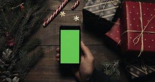 Αρσενικά χέρια που κρατούν το μαύρο smartphone με την πράσινη οθόνη Άλλα χέρια που τοποθετούν μερικά παρόντα πεδία στον πίνακα Κι φιλμ μικρού μήκους