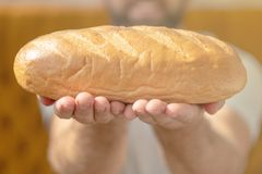 Αρσενικά χέρια που κρατούν το πρόσφατα ψημένο σιταρένιο ψωμί στοκ φωτογραφία με δικαίωμα ελεύθερης χρήσης