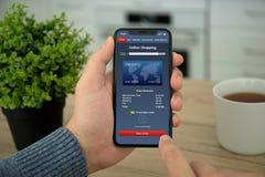 Αρσενικά χέρια που κρατούν το τηλέφωνο με app τις σε απευθείας σύνδεση αγορές στην οθόνη Στοκ εικόνα με δικαίωμα ελεύθερης χρήσης