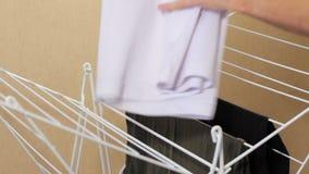 Αρσενικά χέρια που κρεμούν έξω τα ενδύματα στο στεγνωτήρα Ξεραίνοντας πλυμένα ενδύματα Ένα άτομο κάνει τις οικιακές μικροδουλειές φιλμ μικρού μήκους