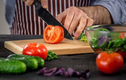 Αρσενικά χέρια που κόβουν τα λαχανικά για τη σαλάτα Στοκ Εικόνες