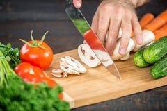 Αρσενικά χέρια που κόβουν τα λαχανικά για τη σαλάτα Στοκ φωτογραφία με δικαίωμα ελεύθερης χρήσης