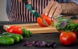 Αρσενικά χέρια που κόβουν τα λαχανικά για τη σαλάτα Στοκ Φωτογραφίες