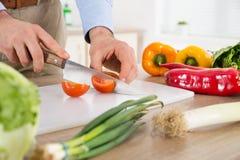 Αρσενικά χέρια που κόβουν την ντομάτα Countertop Στοκ εικόνα με δικαίωμα ελεύθερης χρήσης