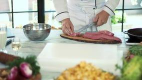 Αρσενικά χέρια που κόβουν το ακατέργαστο κρέας απόθεμα βίντεο