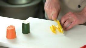 Αρσενικά χέρια που κόβουν το πιπέρι κουδουνιών φιλμ μικρού μήκους