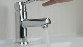 Αρσενικά χέρια που κλείνουν καλυμμένη τη χρώμιο βρύση του νερού απόθεμα βίντεο