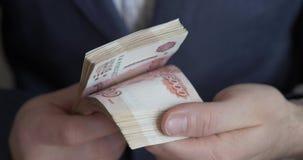 Αρσενικά χέρια που μετρούν τα χρήματα Ρωσικά τραπεζογραμμάτια χρημάτων 5.000 ρουβλιών απόθεμα βίντεο