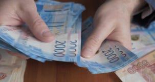 Αρσενικά χέρια που μετρούν τα χρήματα Ρωσικά τραπεζογραμμάτια χρημάτων 2.000 ρουβλιών φιλμ μικρού μήκους