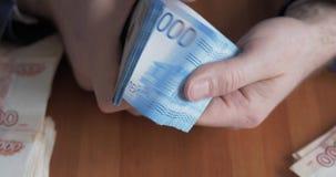 Αρσενικά χέρια που μετρούν τα χρήματα Ρωσικά τραπεζογραμμάτια χρημάτων 2.000 ρουβλιών απόθεμα βίντεο