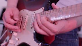 Αρσενικά χέρια που παίζουν την ηλεκτρική κιθάρα Άτομο με ένα μουσικό όργανο Riffs και χορδές Κιθαρίστας της ζώνης βράχος-ν-ρόλων  απόθεμα βίντεο