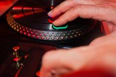 Αρσενικά χέρια που παίζουν το DJ με την περιστροφική πλάκα παιχνιδιών σε ένα κόμμα Στοκ Εικόνα