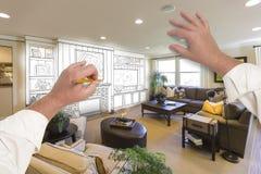 Αρσενικά χέρια που σύρουν το κέντρο ψυχαγωγίας πέρα από τη φωτογραφία του σπιτιού διά Στοκ Εικόνες