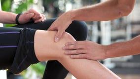 Αρσενικά χέρια που τρίβουν το θηλυκό γόνατο φιλμ μικρού μήκους