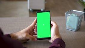 Αρσενικά χέρια που τυλίγουν στο smartphone με την πράσινη χλεύη χρώματος οθόνης επάνω στο γραφείο του φιλμ μικρού μήκους