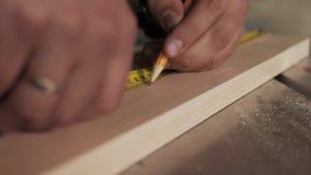 Αρσενικά χέρια που χρησιμοποιούν ένα κίτρινο μέτρο ταινιών για να μετρηθεί ένα κομμάτι του ξύλου φιλμ μικρού μήκους