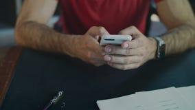 Αρσενικά χέρια που χρησιμοποιούν το τηλέφωνο Κλείστε επάνω του αρσενικού μηνύματος δακτυλογράφησης χεριών στο iphone στην αρχή απόθεμα βίντεο