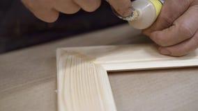 Αρσενικά χέρια που χρωματίζουν την ελαφριά ξύλινη ένωση γωνιών πλαισίων απόθεμα βίντεο