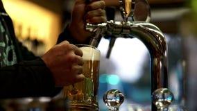Αρσενικά χέρια που χύνουν την μπύρα στην κούπα γυαλιού από τη βρύση Φρέσκια μπύρα σχεδίων στο μπαρ απόθεμα βίντεο