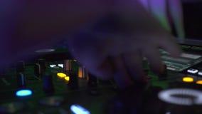 Αρσενικά χέρια στην υγιή κονσόλα του DJ που αναμιγνύει το κόμμα μουσικής σπιτιών τη νύχτα Ελεγκτής του DJ για να αναμίξει τη μουσ φιλμ μικρού μήκους
