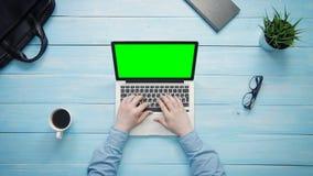 Αρσενικά χέρια τοπ άποψης που λειτουργούν στο φορητό προσωπικό υπολογιστή με την πράσινη οθόνη στο άσπρο γραφείο άνωθεν απόθεμα βίντεο