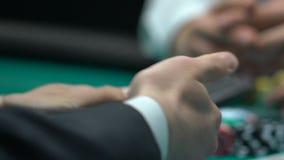 Αρσενικά χρήματα στοιχημάτισης φορέων πόκερ στις χαμηλές κάρτες, απερίσκεπτος ερασιτέχνης παίκτης, κινηματογράφηση σε πρώτο πλάνο απόθεμα βίντεο