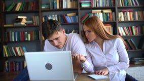 Αρσενικές και γυναίκες σπουδαστές που μελετούν σε ένα lap-top ζεύγος 4 Κ των σπουδαστών που μαθαίνουν από κοινού σπουδαστές που μ απόθεμα βίντεο