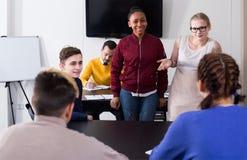 Αρσενικές και γυναίκες σπουδαστές που έχουν τη συνομιλία στην κοιλότητα στοκ φωτογραφίες