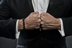 Αρσενικές πυγμές με τις πρησμένες φλέβες και βραχιόλι στο επίσημο υπόβαθρο κοστουμιών Έννοια αντιμετώπισης Χέρι του επιχειρησιακο στοκ εικόνες