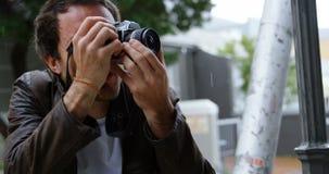 Αρσενικές χτυπώντας φωτογραφίες φωτογράφων με τη κάμερα 4k απόθεμα βίντεο