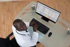 Αρσενική δακτυλογράφηση γιατρών στο πληκτρολόγιο υπολογιστών Στοκ φωτογραφία με δικαίωμα ελεύθερης χρήσης