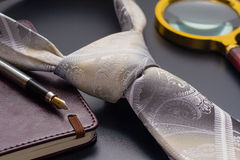 Αρσενική ακόμα ζωή Μια μάνδρα πηγών με ένα σημειωματάριο βρίσκεται σε έναν δεσμό Στοκ Φωτογραφίες
