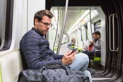 Αρσενική ανάγνωση κατόχων διαρκούς εισιτήριου από την κινητή τηλεφωνική οθόνη στο μετρό Στοκ Εικόνες