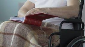 Αρσενική αναπηρική καρέκλα συνεδρίασης, λεύκωμα φωτογραφιών ανοίγματος για να εξετάσει τις εικόνες, προηγούμενες μνήμες απόθεμα βίντεο